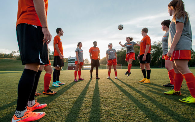 Mens and ladies soccer players at sunset